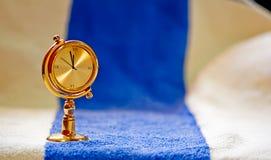 Un orologio di tabella dorato su priorità bassa blu Immagini Stock Libere da Diritti