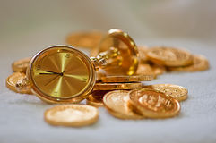 Un orologio di tabella dorato un il mazzo di monete di oro Fotografia Stock Libera da Diritti