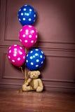 Un orso con le palle blu e rosa sta sedendosi sul pavimento Fotografie Stock