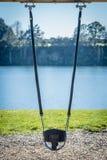 Un oscilación vacío en un patio que pasa por alto un lago Fotografía de archivo libre de regalías