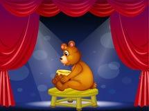 Un oso con un pote de miel que se sienta en la etapa Fotografía de archivo