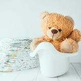 Un oso de peluche en un potty al lado de la pila de pañales imagen de archivo