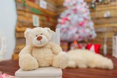 Un oso de peluche se sienta en una silla contra el contexto de un árbol de navidad dentro Fotografía de archivo