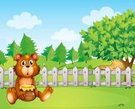 Un oso dentro de la cerca que sostiene un pote de miel Imagenes de archivo