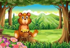 Un oso en el bosque que sostiene un pote de miel Foto de archivo