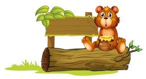 Un oso que se sienta en un tronco Foto de archivo libre de regalías