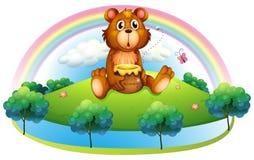 Un oso que sostiene un pote de miel en la colina Imágenes de archivo libres de regalías