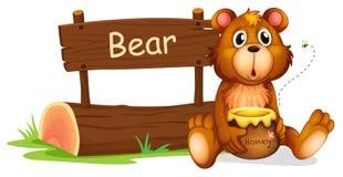 Un oso que sostiene una miel al lado de un letrero de madera Imagen de archivo libre de regalías