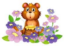 Un oso que sostiene una miel en el jardín de flores Fotos de archivo libres de regalías