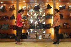 Un ospite al negozio di scarpe per scegliere il modello delle scarpe Fotografie Stock Libere da Diritti