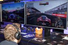 Un ospite della fiera campionaria sta giocando il gioco delle automobili 2 del progetto fotografia stock
