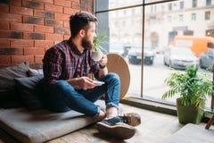 Un ospite maschio che si siede nel caffè immagine stock