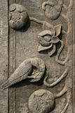 Un pájaro y las flores fueron esculpidos en un pilar en el patio de un templo budista cerca de Hanoi (Vietnam) Foto de archivo