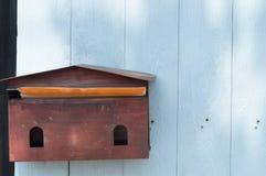Un pâle - la boîte aux lettres rouge accrochant sur le bleu wodden le fond Photographie stock libre de droits