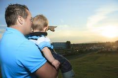 Un père avec est fils au coucher du soleil Photo stock