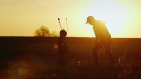 Un père avec un petit fils plantent ensemble un arbre Au coucher du soleil, belles silhouettes Concept - une nouvelle vie, une fa banque de vidéos