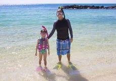 Jeune famille naviguant au schnorchel dans l'océan ensemble Photographie stock libre de droits