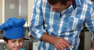 Un père et son fils préparent des pâtisseries clips vidéos