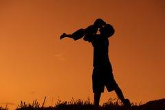 Un père et un fils jouant dehors au coucher du soleil Images stock