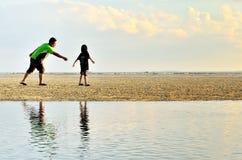Un père et une fille courant le long de la plage Photographie stock
