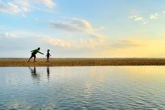 Un père et une fille courant le long de la plage Photo libre de droits