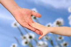 Un père tient la main d'un petit enfant sur un fond bleu Image stock