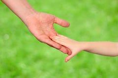 Un père tient la main d'un petit enfant sur un fond vert Photos stock