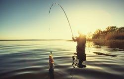 Un pêcheur avec une canne à pêche dans sa main et un poisson photos libres de droits