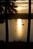 Un pêcheur dans le bateau au coucher du soleil sur le lac Photos stock