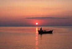 Un pêcheur dans un bateau Images libres de droits