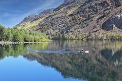 Un pêcheur dans un bateau au milieu du lac Image libre de droits