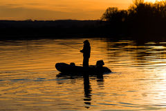 Un pêcheur dans une canne à pêche de bateau Photos libres de droits