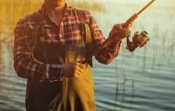 Un pêcheur dans une chemise rouge pêche pour tourner dans un étang d'eau douce Photo libre de droits