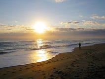 Un pêcheur de ressac de lever de soleil photographie stock libre de droits