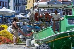 Un pêcheur et un ami examinent des filets de pêche pour déceler les trous dans le port de l'île grecque de Kastellorizo Photos libres de droits