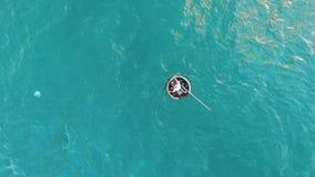 Un pêcheur nage dans un bateau par la mer banque de vidéos