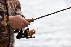 Un pêcheur pêche un poisson Mains d'un pêcheur avec un plan rapproché disponible de tige de rotation Photos stock