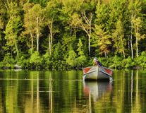 Un pêcheur retournant au lac image stock