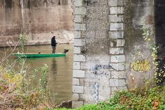 Un pêcheur solitaire dans un bateau sous le pont Image libre de droits