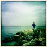 Un pêcheur solitaire par les roches Photos libres de droits