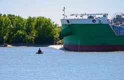 Un pêcheur sur le fond du bateau Images stock