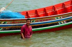 Un pêcheur thaïlandais se tient dans l'eau à côté de son bateau Pattani Thaïlande Image libre de droits