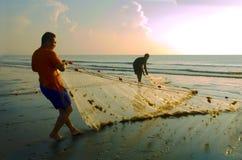 Un pêcheur tire vers le haut un voisin net une plage Image libre de droits