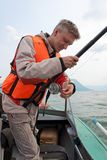 Un pêcheur utilisant un gilet de sauvetage. Image libre de droits