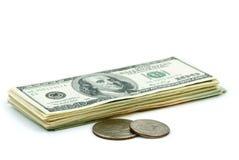 Un pacchetto di $100 banconote e di due monete Fotografia Stock Libera da Diritti