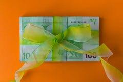 Un pacchetto di cento euro banconote con il arco-nodo verde sullo scrittorio, sul regalo o sui dividendi arancio concetto, soldi  fotografie stock