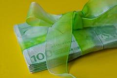 Un pacchetto di cento euro banconote con il arco-nodo verde sullo scrittorio, sul regalo o sui dividendi gialli concetto, soldi d immagini stock