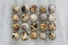 Un pacchetto di 20 uova di quaglia su fondo d'annata bianco Fotografia Stock
