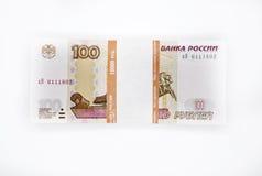 Un pacco di 100 banconote dei pezzi 100 cento rubli di banconota della Banca della Russia sulle rubli russe del fondo bianco Fotografia Stock Libera da Diritti