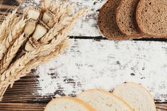 Un pacco di grano e papavero e farina sparsa e fette di pane sulle vecchie plance di legno Immagini Stock Libere da Diritti